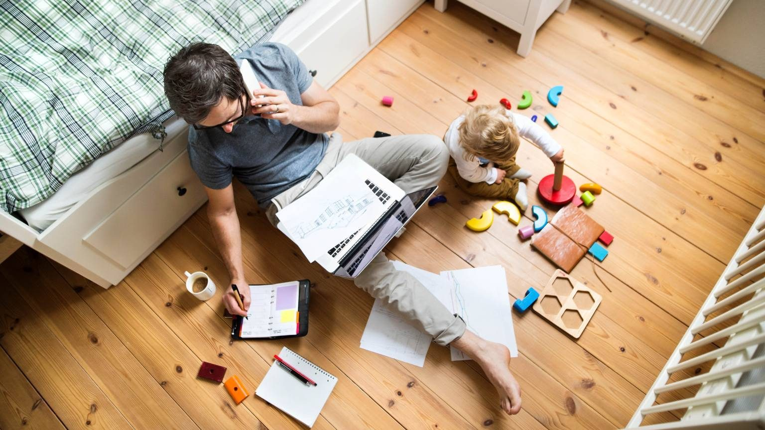 Dad working from home on laptop with paper spread around on floor while child plays