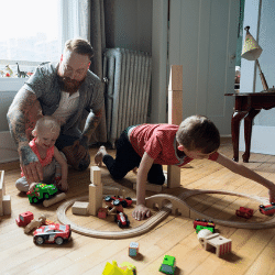 Father and children playing with wood blocks and toy train