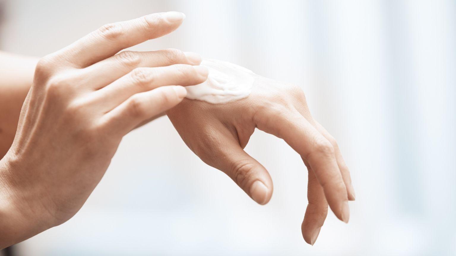 Woman using moisturizer on hands