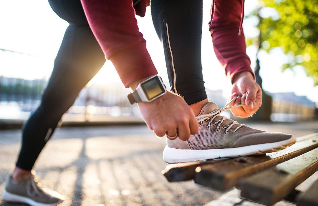 Runner tying laces wearing smartwatch