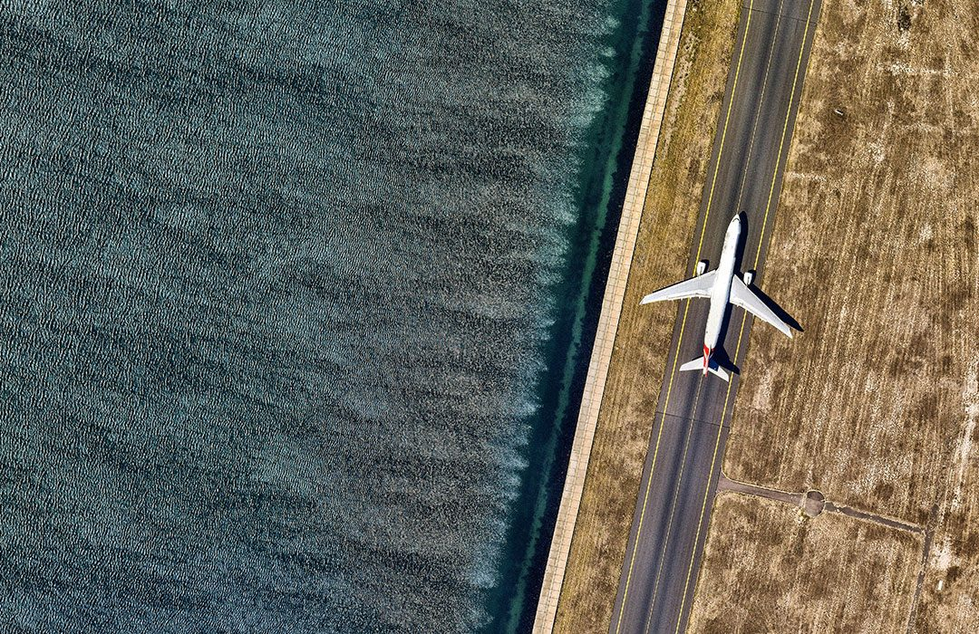 Plane On A Runway Next To Water