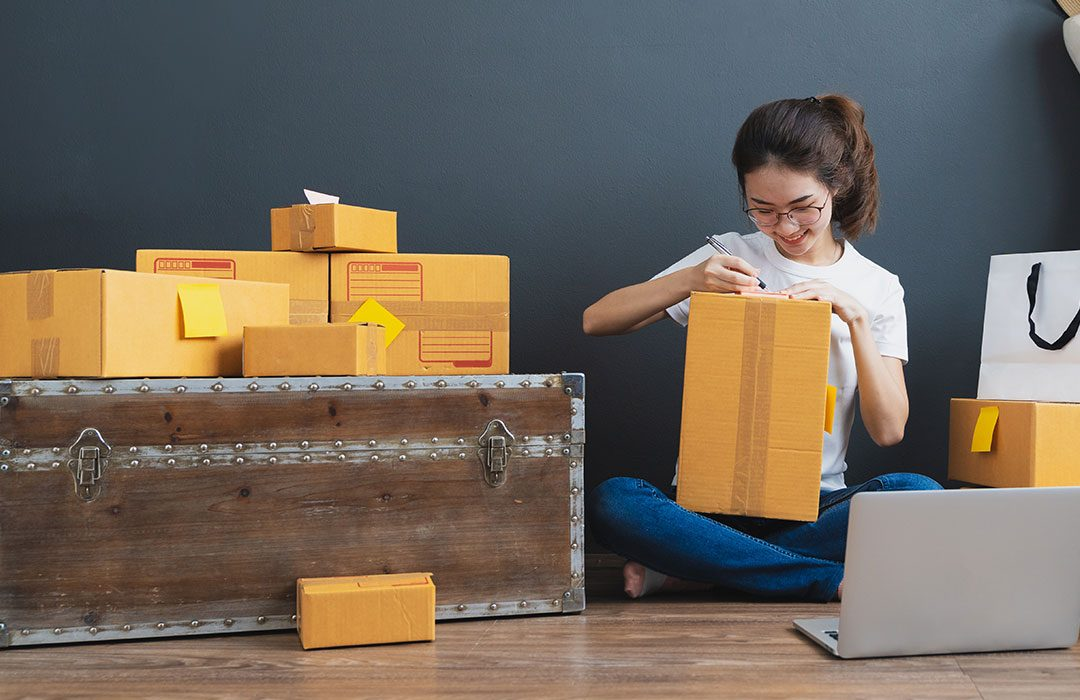 Woman sitting on the floor opening packages