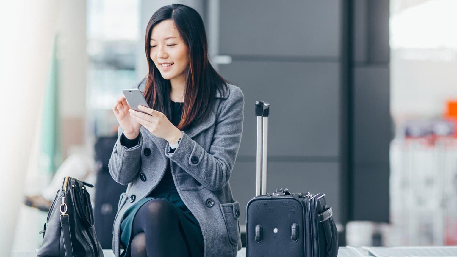 woman checking prepaid phone on airport