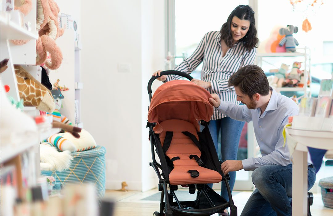 couple shopping for a pram in a baby store