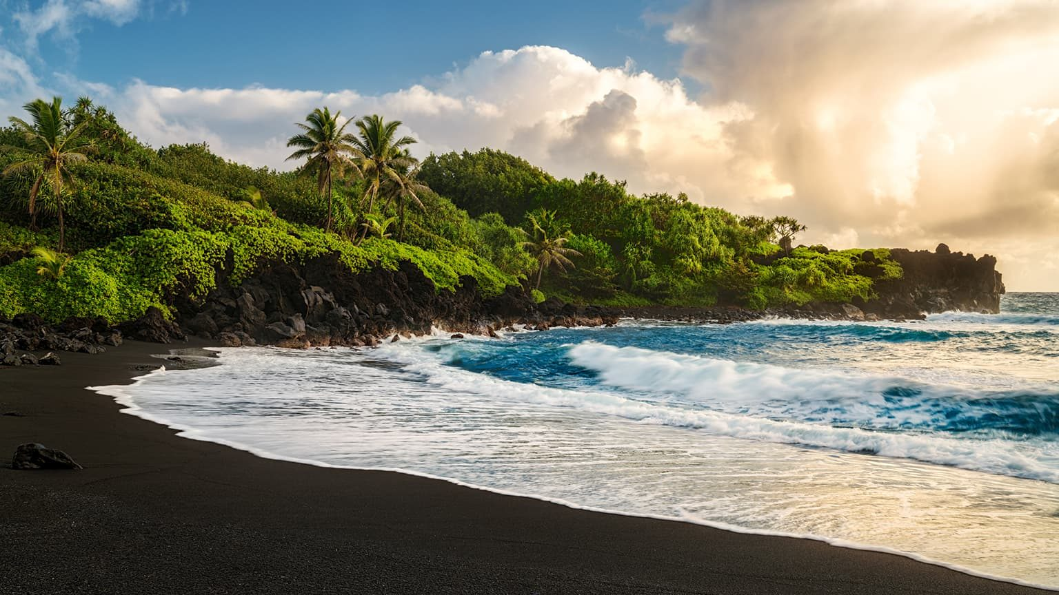 Waianapanapa Beach showing volcanic black sand with waves and sun shining