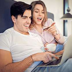 A couple having coffee on bed in  front of a laptop holding credit card