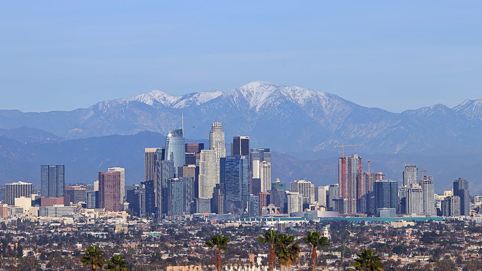 Skyline of Los Angeles with snowcapped moutain as background