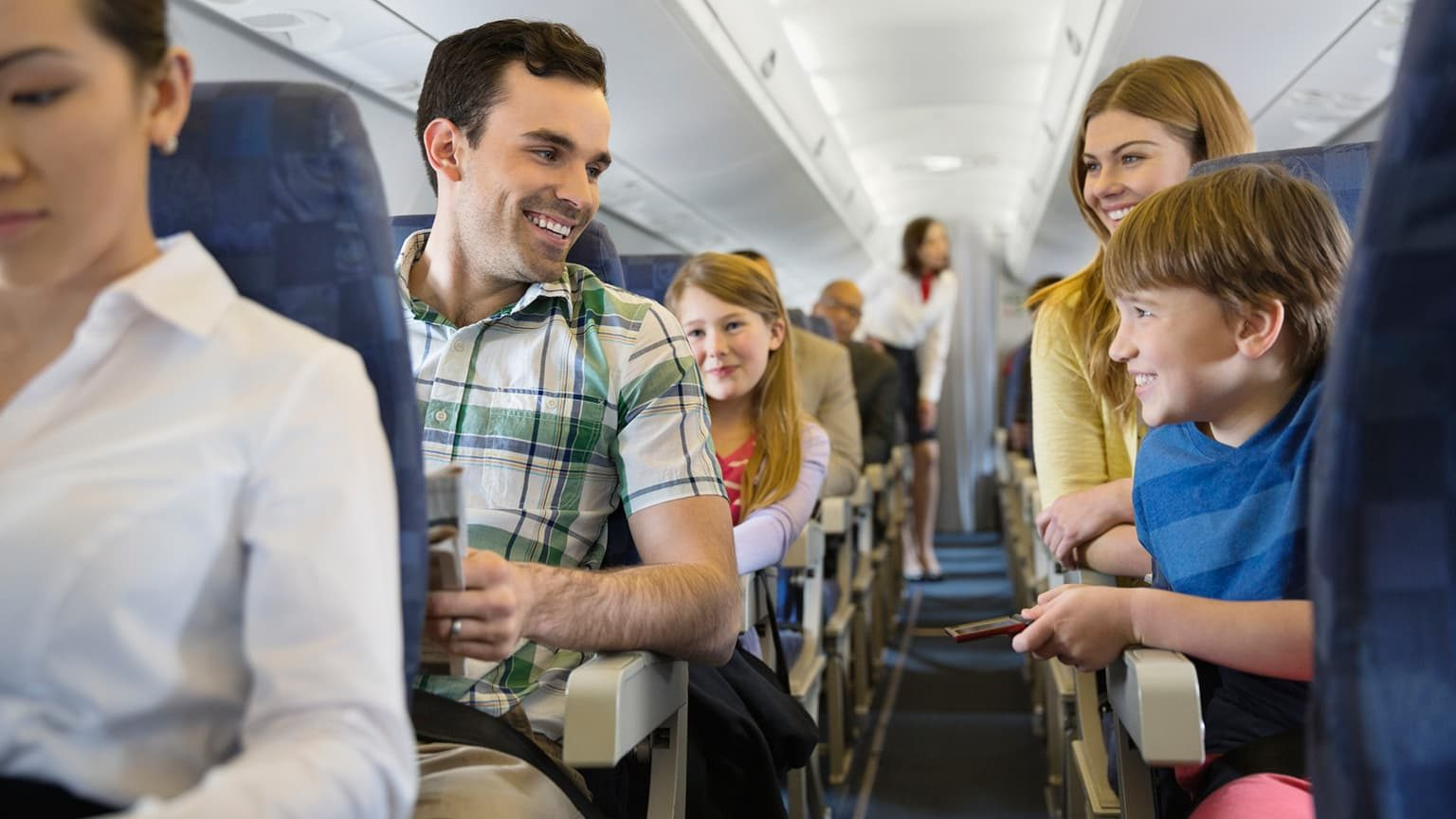 A young  family seating by the aisle of an airplane