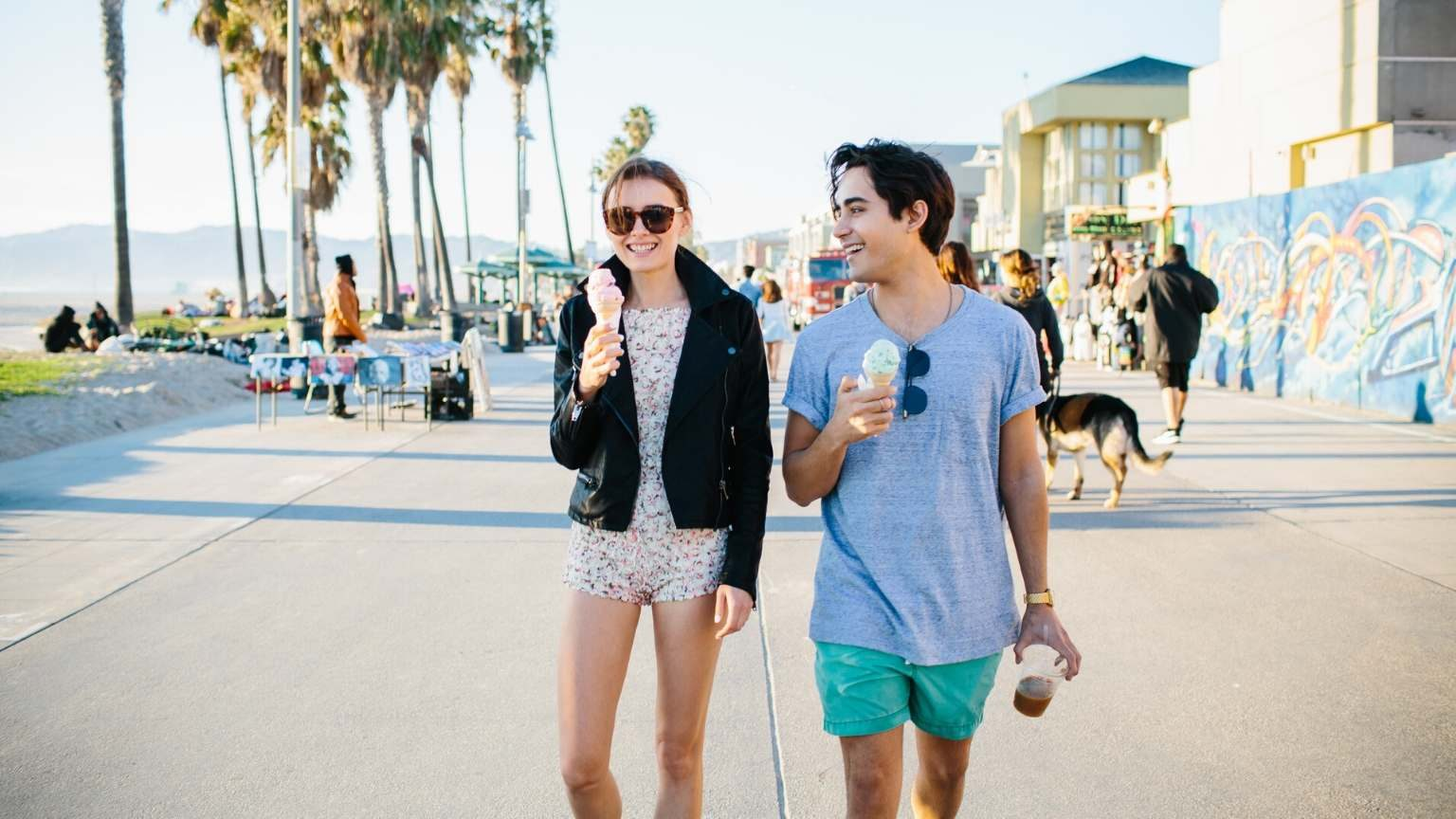 Young couple walking on the sidewalk eating icecream
