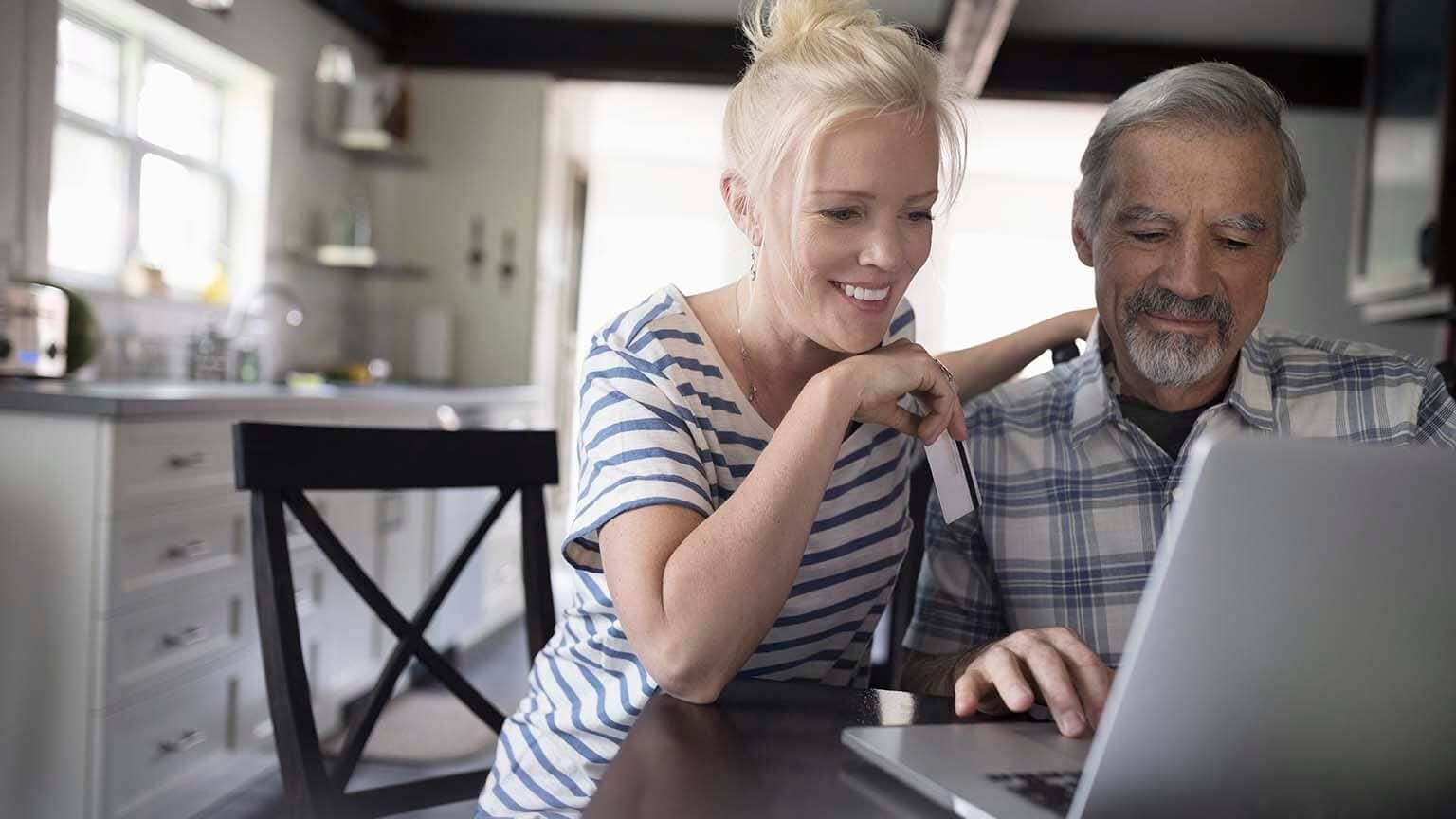 Daughter with senior father checking online bank account