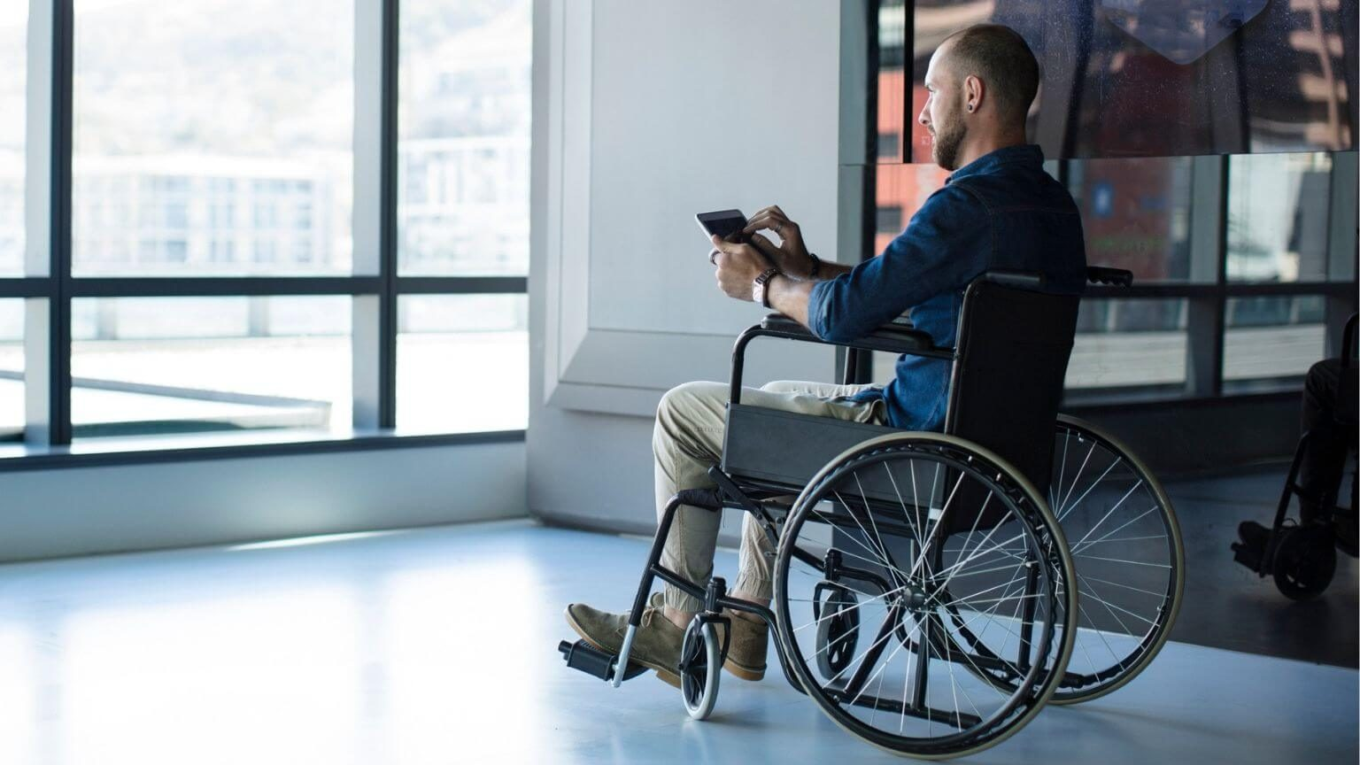 Man in wheelchair looking out of window in office using tablet