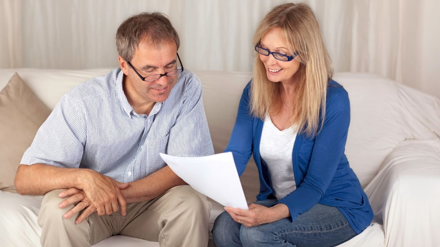 Mature couple sat on couch checking a form