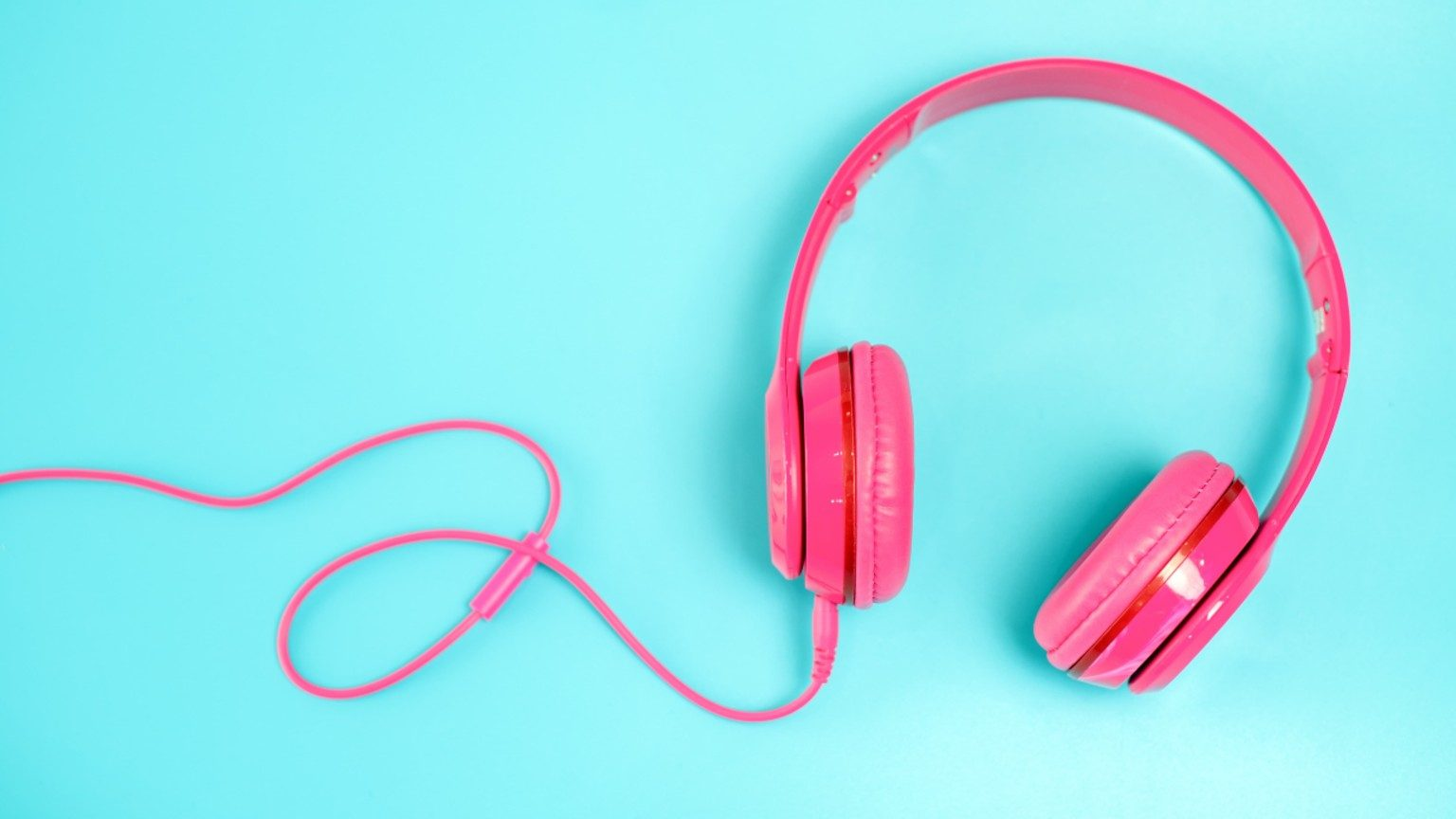 Pink headphone on light with blue background