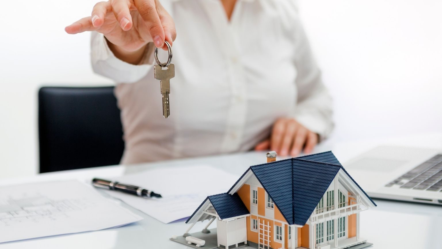 Real State Agent holding key with house model