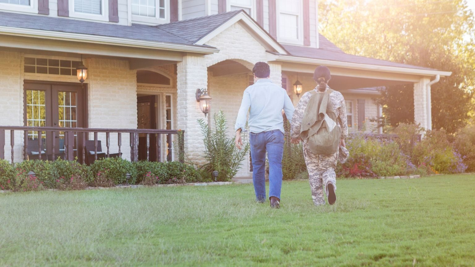 Rear view of husband and military wife entering home together