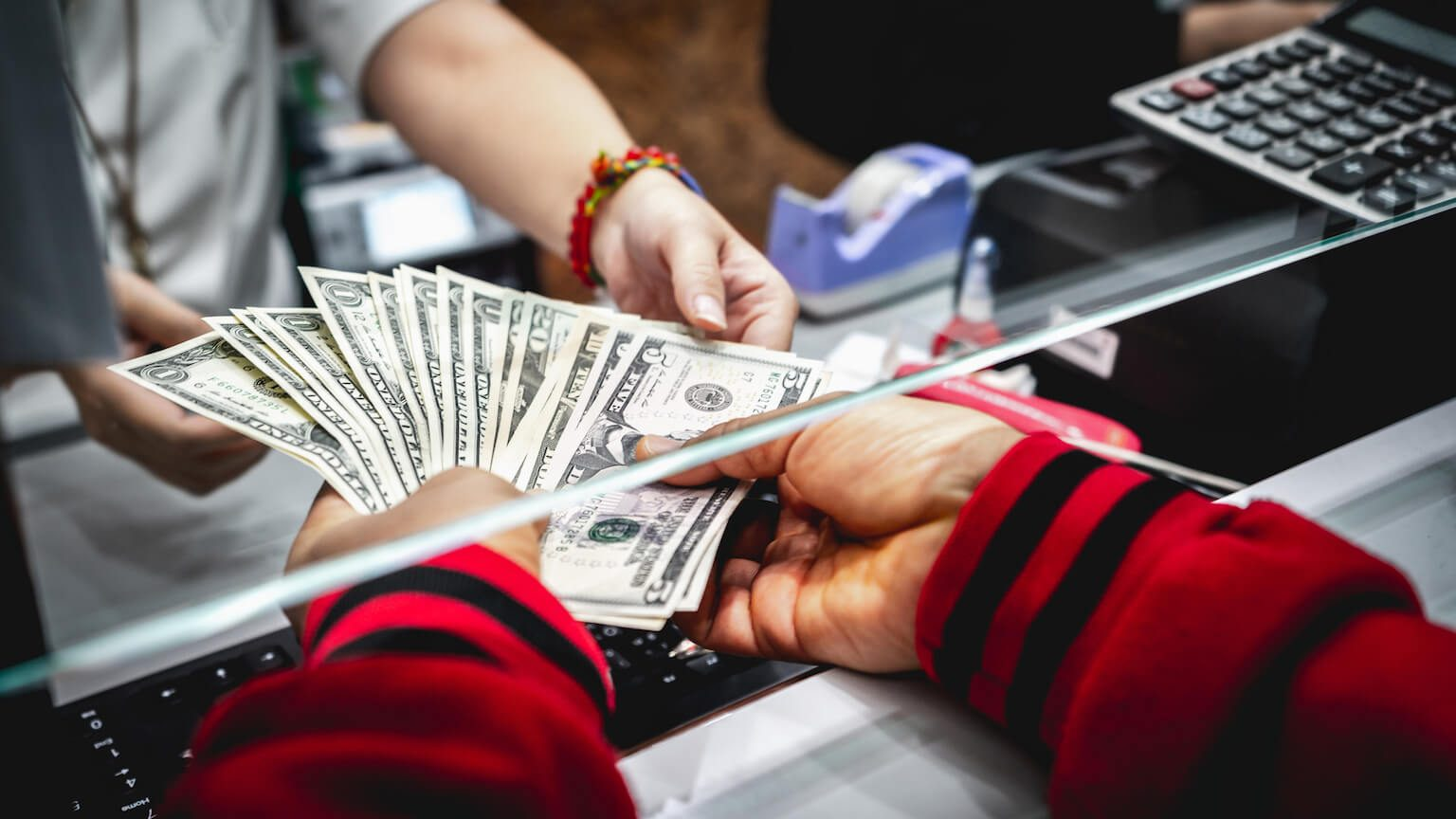 Hands receiving cash at bank teller
