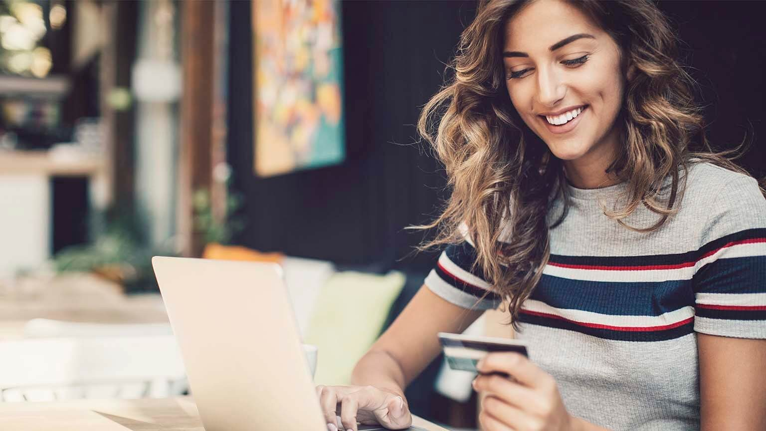 Smiling young woman holding a debit card and typing on a laptop