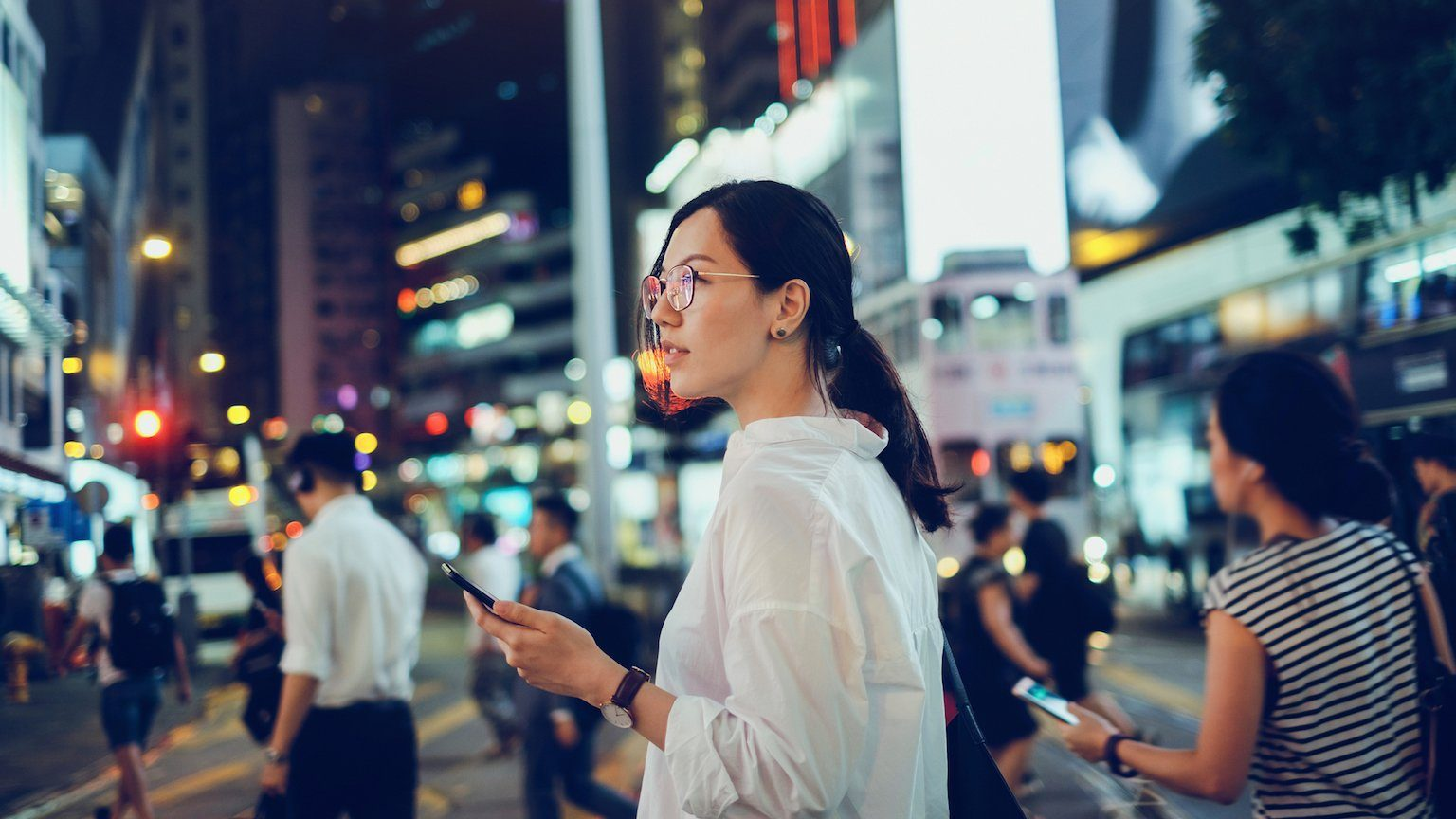 Woman holding a phone in a busy city.