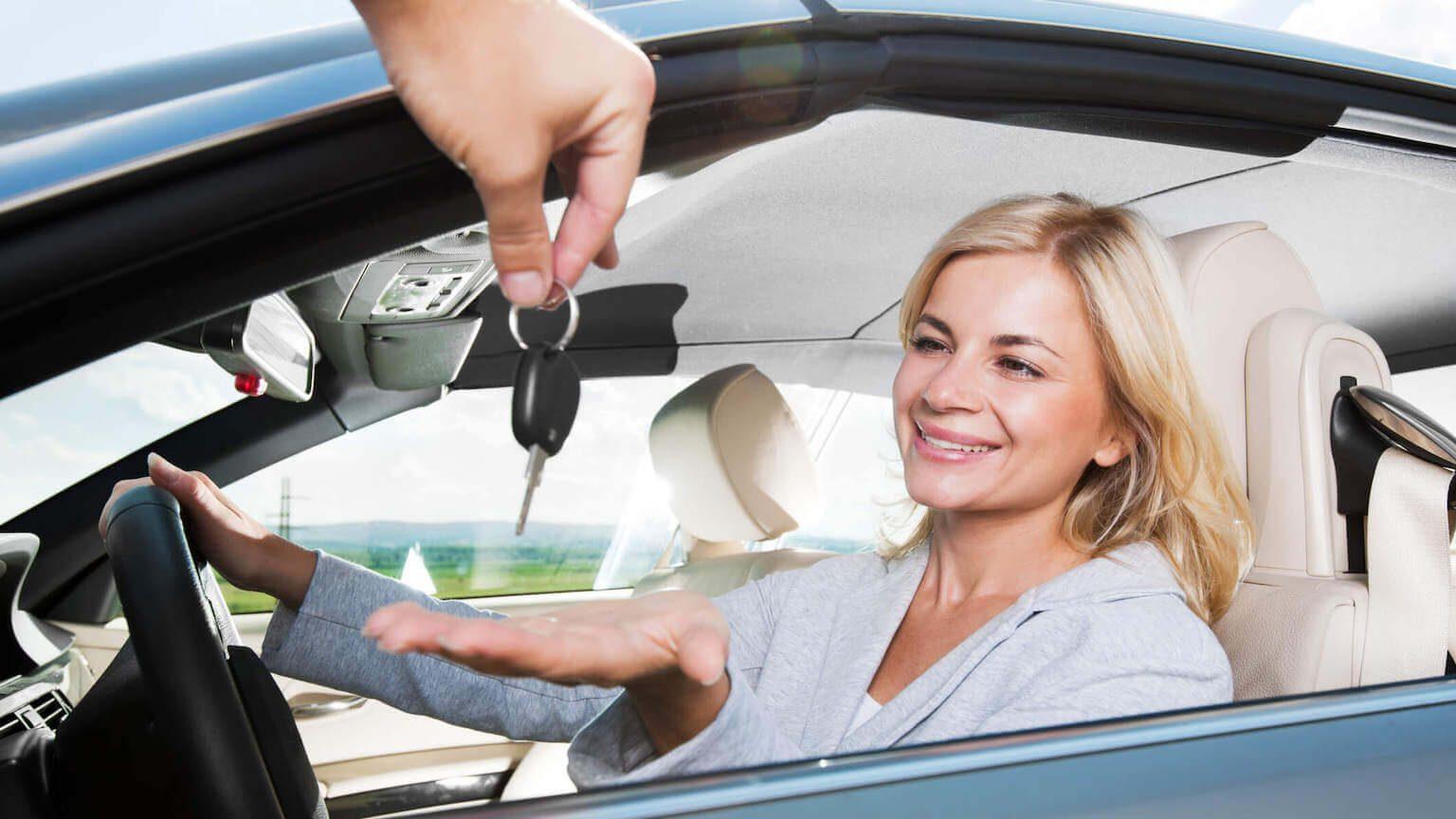 Woman receiving keys in a new car