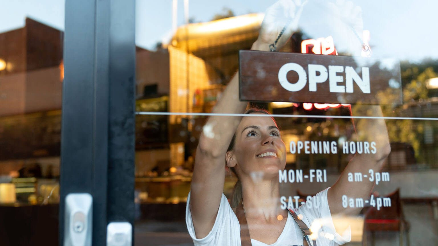 Happy business owner hanging open sign