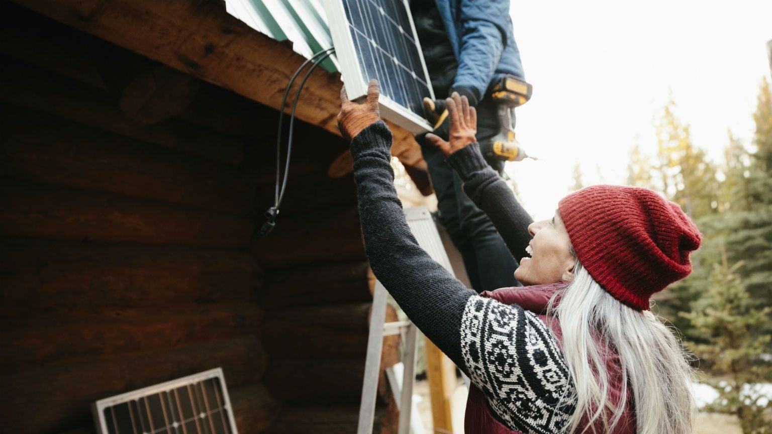 Woman helping man install solar panels on home