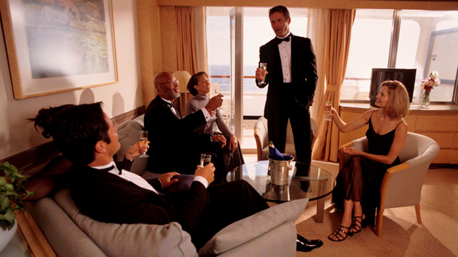Group of friends in formal wear enjoying champagne in luxury cabin on a cruise ship