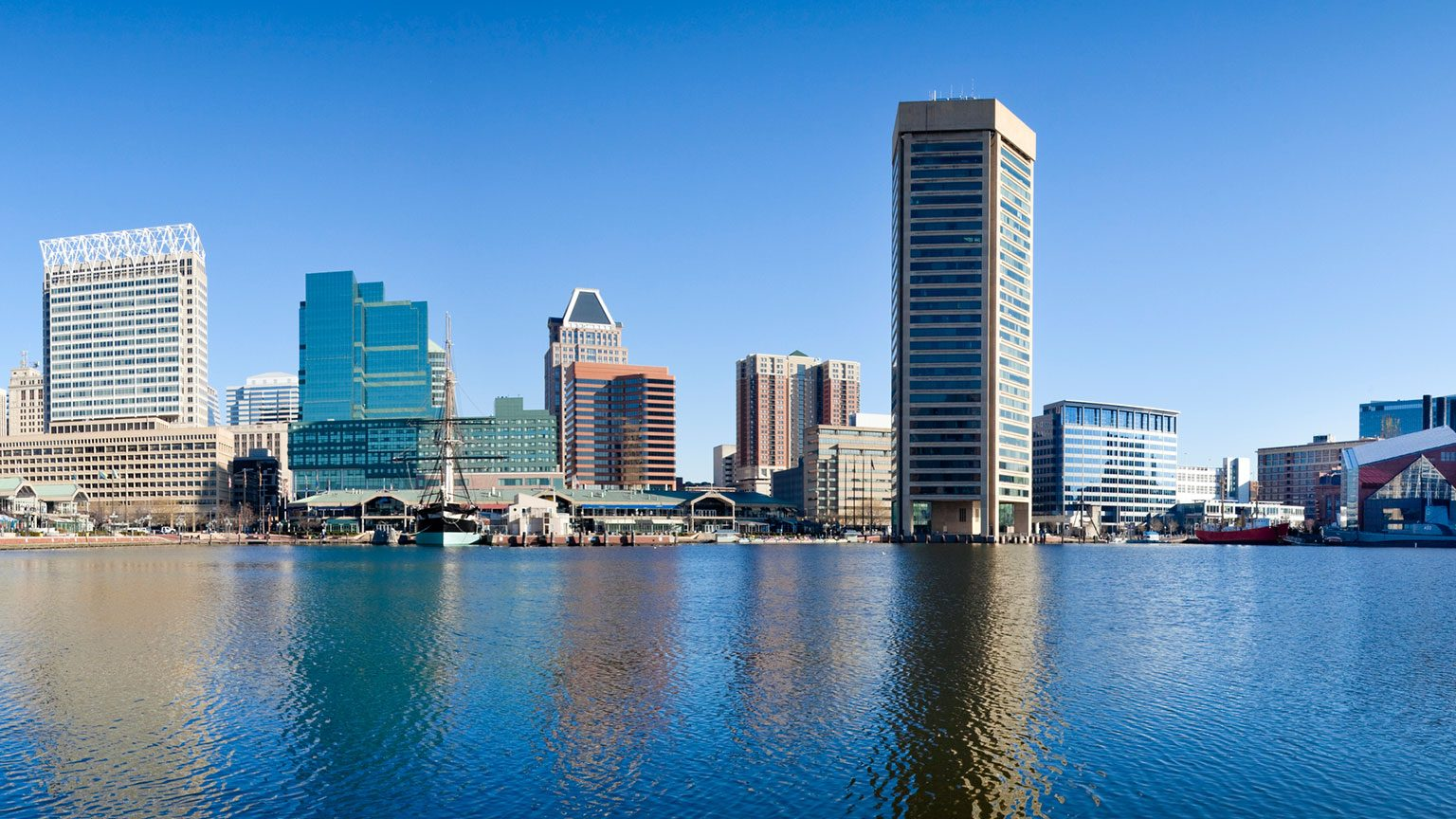Baltimore inner harbor with city skyline during the day.