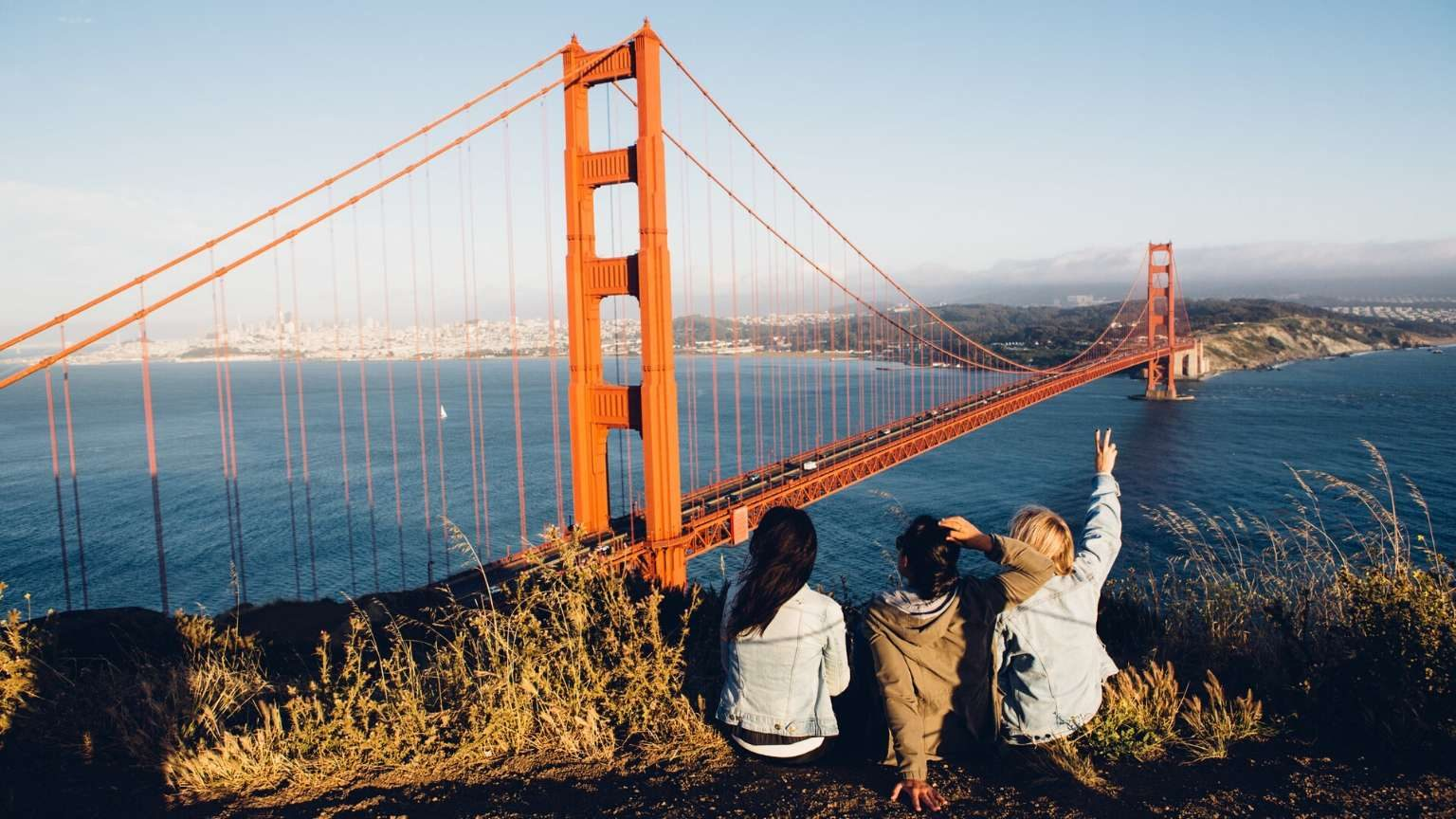 Californians sitting on a hill facing the bridge