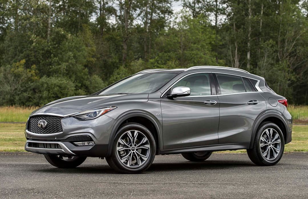 Infiniti QX30 2019 car on a road with trees at the background