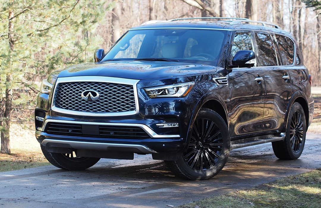 Infiniti QX80 2019 car on a road with trees and grass on the background