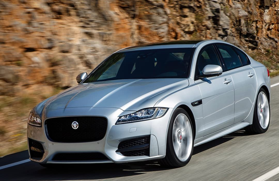 Jaguar XF 2019 car in motion with rock formation at the background