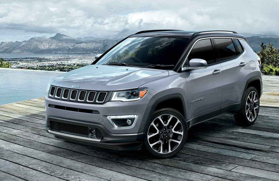 Jeep Compass 2019 car parked at a dock beside a lake and mountains behind