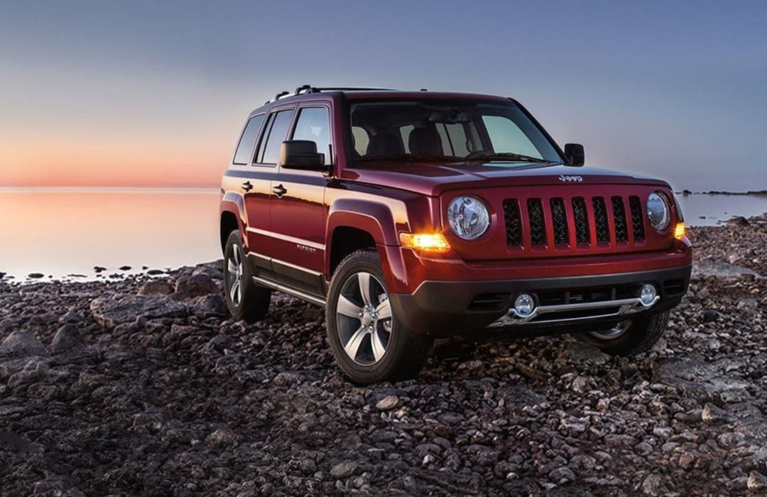 Jeep Patriot 2019 on a rocky beach with sunset behind