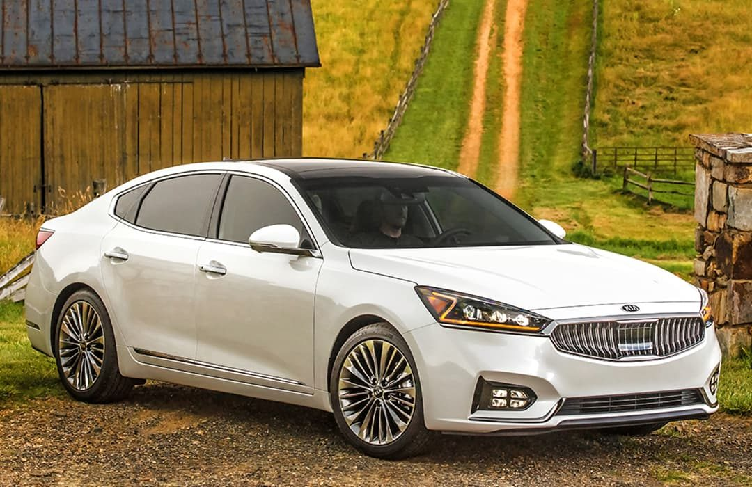 Kia Cadenza 2019 in countryside location with a road behind, with a male driver