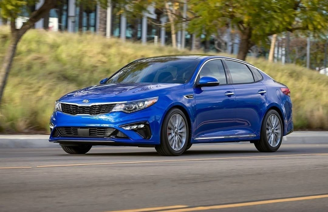 Kia Optima 2019 car in motion on a highway with trees and grass in the background