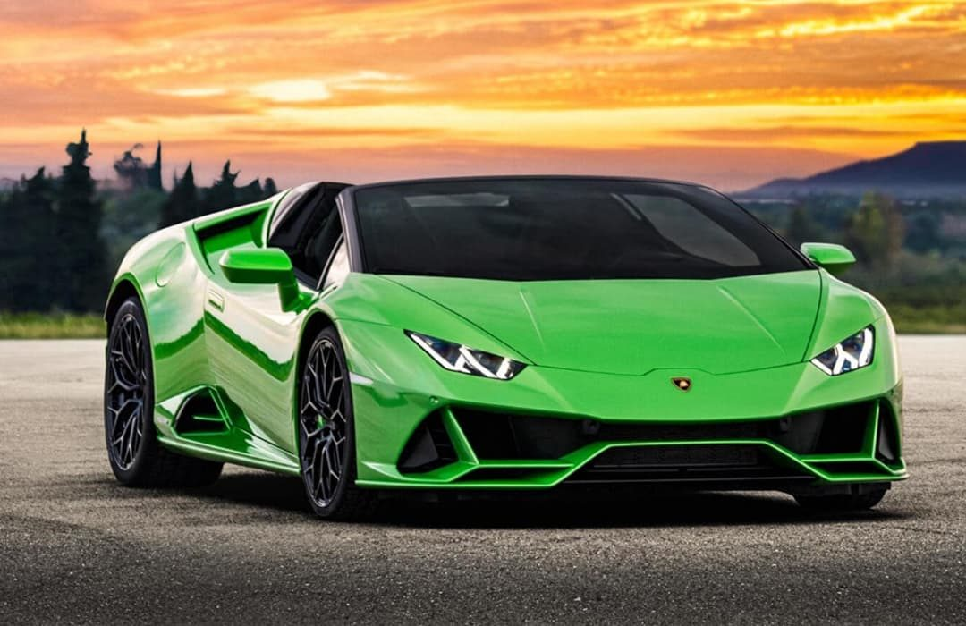 Lamborghini Huracan green car parked on a street with sunset and trees behind