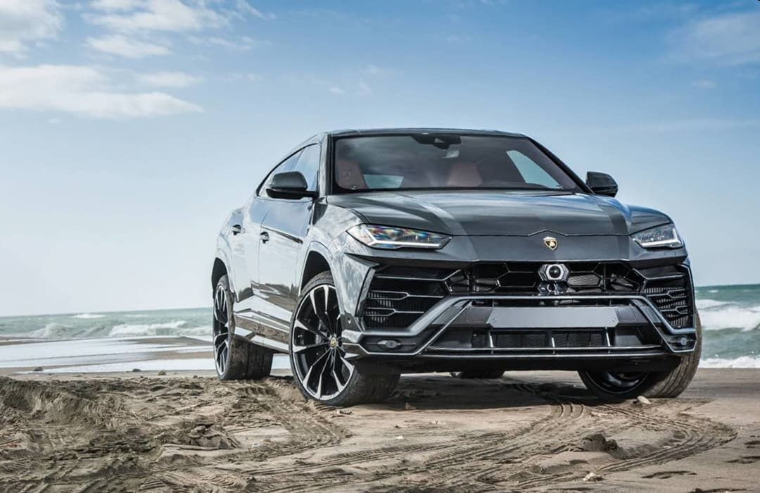 Lamborghini Urus 2019 black car parked at the beach with the sea behind