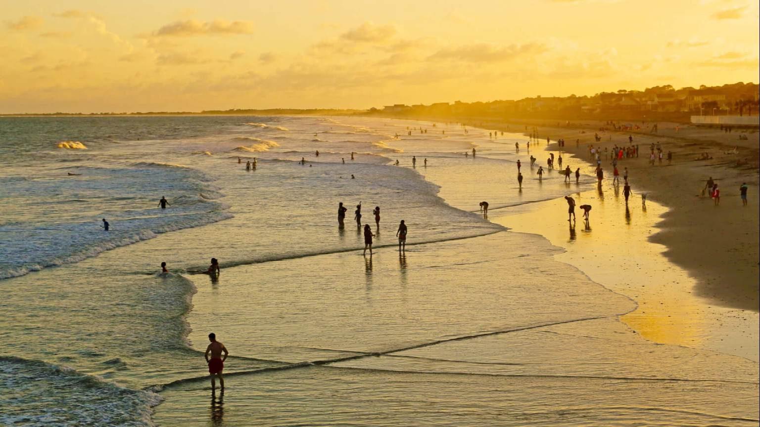 People playing on Folly Beach in Charleston, South Carolina at sunset