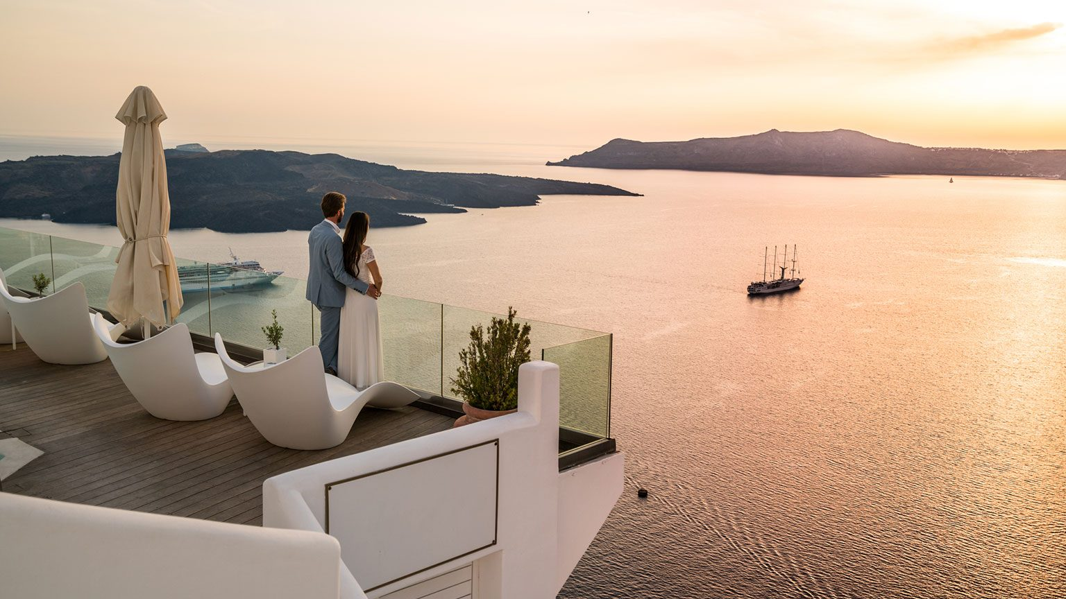 Couple on balcony overlooking water in Greece at sunset