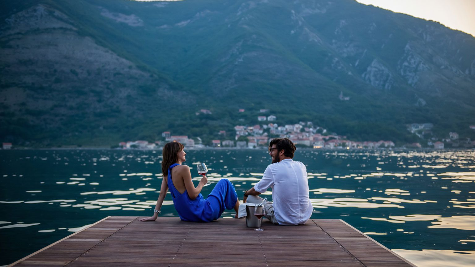 Couple sitting on a dock enjoying champagne on a romantic getaway