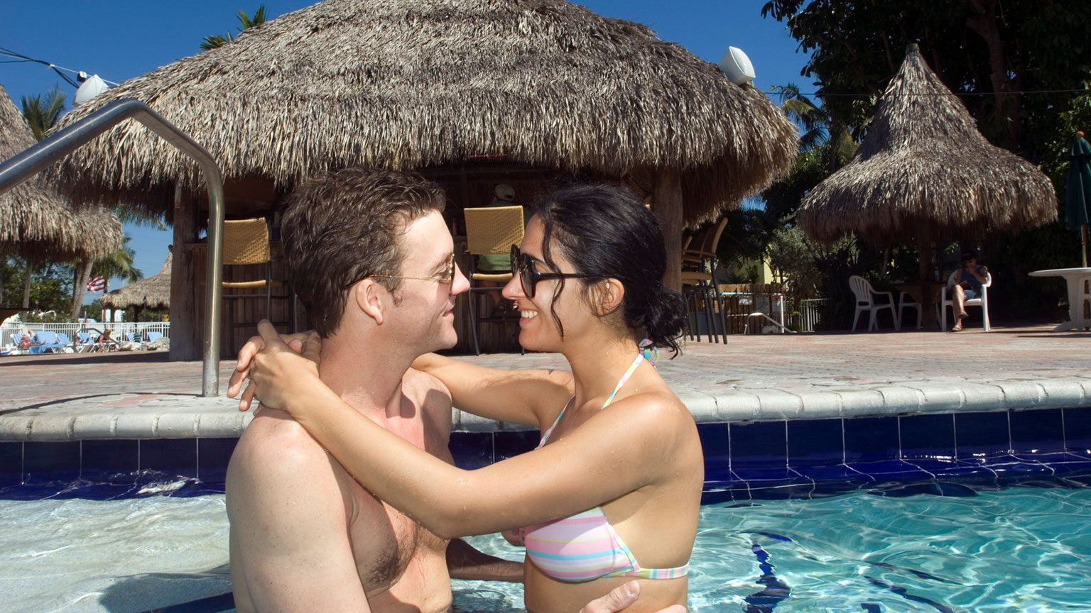 Happy couple embracing in hotel pool.