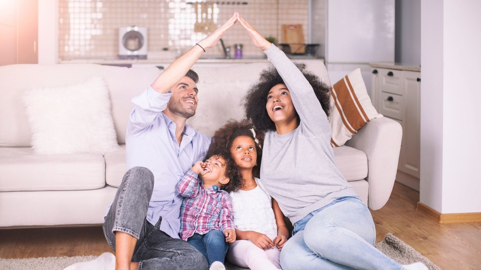 A family in their living room forming a house with their hands