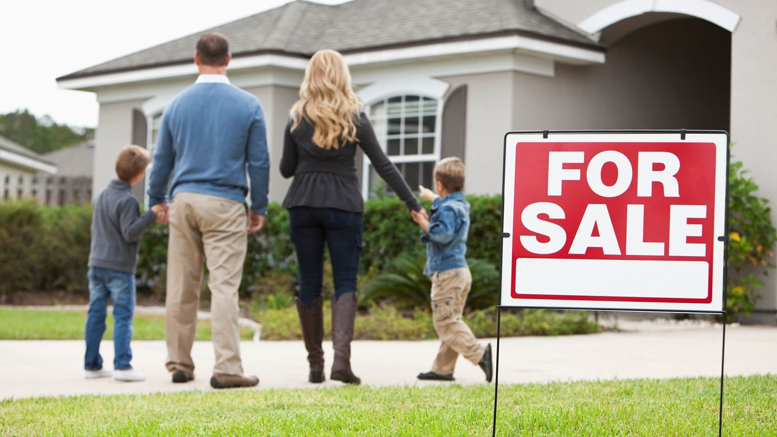 Family with two boys standing in front of house with for sale sign in front yard