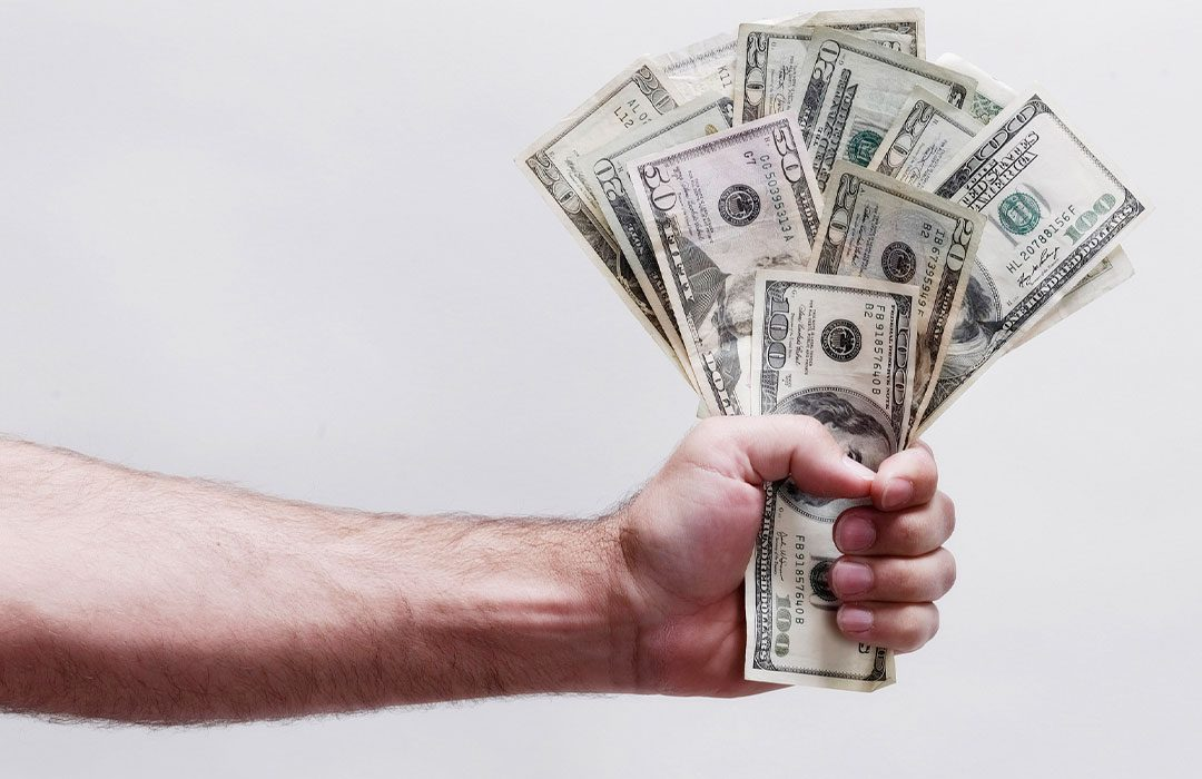 Picture of a man handing over a wad of cash