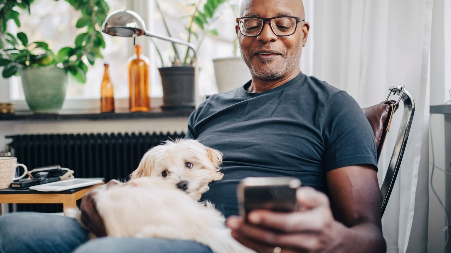 Man with his dog and smartphone in his hand