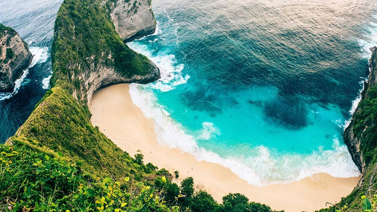 Aerial view of Bali beach in a cove with high cliffs