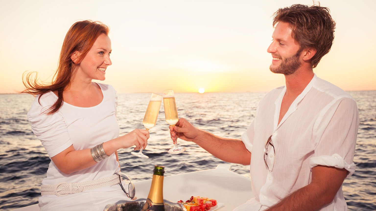 Happy couple on a cruise enjoying a champagne toast at sunset