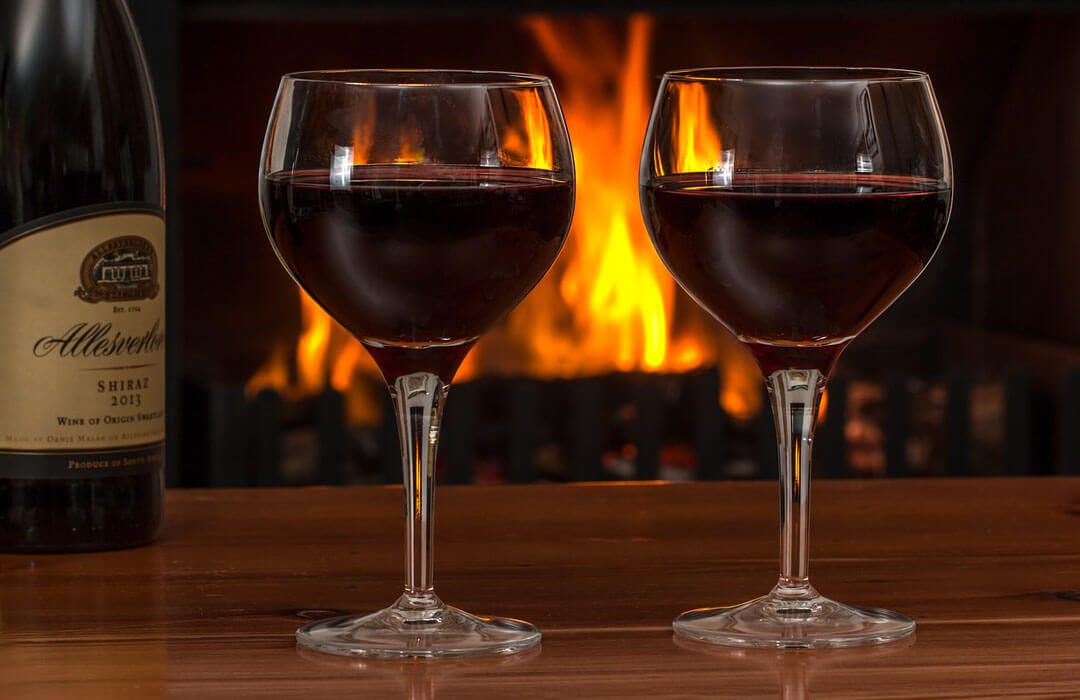 Two glasses of wine in front of fireplace