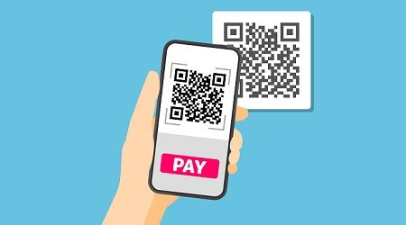 Hand holding smartphone to scan QR code on paper for detail