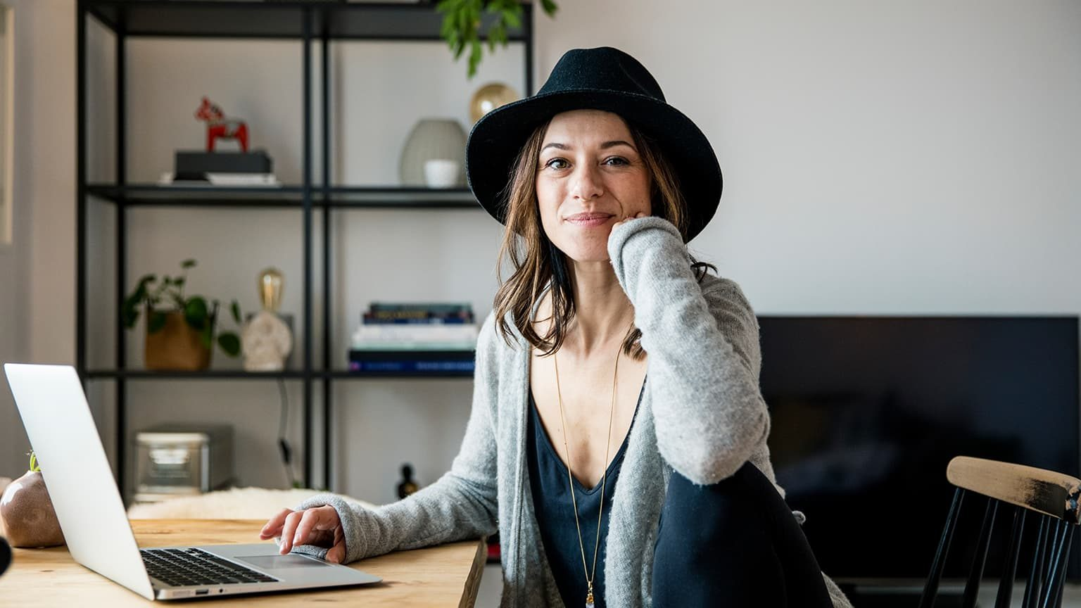 Women with hat smiling while sitting at a desk with a laptop